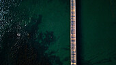 Minimalist photograph with aerial view of long pier in sea
