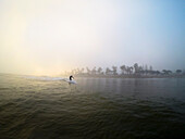 Surfer riding wave in foggy weather under clear sky at sunrise