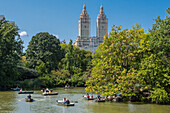 rowers rowing a boat on the lake in central park with the two towers of the san remo apartment building in the background, manhattan, new york city, new york, united states, usa