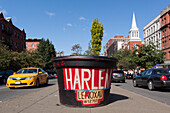 giant pot of flowers in the colors of harlem along lenox avenue with a new york taxi and the bell of a gospel church, harlem, manhattan, new york city, new york, united states, usa