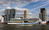 cruise boat in front of the hotel new york against a background of contemporary architecture, city center, rotterdam, holland, the netherlands