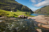 stream at the foot of a vegetal roofed church at the end of a fjord, the sea in the distance, saksun, streymoy, faroe islands, denmark