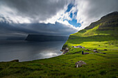 stormy sky over the steep slopes of the fjords, ray of sunlight lighting up a farm on a verdant slope, kalsoy, faroe islands, denmark