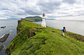 hiker on a trail along the verdant cliffs of the island of mykines near a lighthouse, mykines, faroe islands, denmark