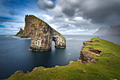 hiker standing on the edge of a grass-covered cliff contemplating the arched sea stack of drangarnir, vagar, faroe islands, denmark