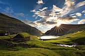 traditional houses with vegetal roofs in a verdant fjord, the last rays of the setting sun over the distant cliffs, saksun, streymoy, faroe islands, denmark