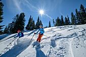 Two women backcountry-skiing descending through powdersnow, Predigtstuhl, Chiemgau Alps, Chiemgau, Upper Bavaria, Bavaria, Germany