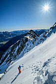 Woman backcountry-skiing ascending on foot on steep face, Hochmiesing, Spitzing, Bavarian Alps, Upper Bavaria, Bavaria, Germany