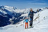 Man and woman backcountry-skiing ascending towards Rastkogel, Zillertal Alps in background, Rastkogel, Tuxer Alps, Tyrol, Austria