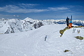 Man and woman backcountry-skiing standing at summit of Halslspitze and looking towards Tuxer Alps, Halslspitze, Tuxer Alps, Tyrol, Austria