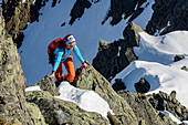 Woman backcountry-skiing climbing rock-ridge, Steintalspitze, Sellrain, Stubai Alps, Tyrol, Austria
