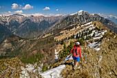 Woman hiking over ridge, Monte Caret, lake Garda, Garda Mountains, Trentino, Italy