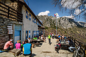 Many persons sitting at hut rifugio Nino Percin, rifugio Nino Percin, lake Garda, Garda Mountains, Trentino, Italy