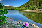 Three persons sitting at beach of Alb-Stausee and having a break, Alb-Stausee, Albsteig, Black Forest, Baden-Wuerttemberg, Germany