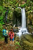 Two women hiking looking towards waterfall, waterfall Hoellbach, Albsteig, Black Forest, Baden-Wuerttemberg, Germany