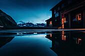 Bergpanorama in Abendstimmung spiegelt sich auf Terasse der Memminger Hütte,E5, Alpenüberquerung, 2. Etappe, Lechtal, Holzgau, Tirol, Österreich, Kemptner Hütte zur Memminger Hütte