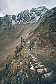 Climber on the descent on long distance hiking path, E5, Alpenüberquerung, 6th stage, Vent,Niederjochbach, Similaun hut, Schnalstal, Vernagt reservoir, Meran