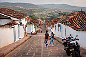 young couple crosses steep alley with fantastic view at the surrounding area of Barichara, Departmento Santander, Colombia, Southamerica