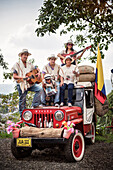 Colombian Family posing for a photo at red 4x4 Vehicle, Salento, UNESCO World Heritage Coffee Triangle, Departmento Quindio, Colombia, Southamerica