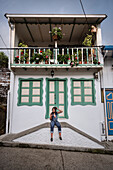 young woman getting her hair done with smartphone camera in front of colonial building, Salento, UNESCO World Heritage Coffee Triangle, Departmento Quindio, Colombia, Southamerica