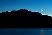 Car tail lights as light strips in front of the Kampenwand on Lake Chiemsee, the moon shines