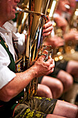Musician in bavarian costume plays tenor horn; further musicians blurry in the background; in detail