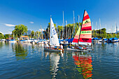 Sailors in the Port field on the Chiemsee Wieser Bay; two sailing boats are reflected in the clear water; framed by blue skies and green trees