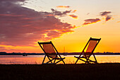 Two sun loungers and boats in the last evening light at the Chiemsee beach at Feldwies