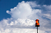 Storm warning light on the Chiemsee in Prien, behind white clouds in the blue sky