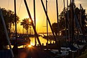 View between sail masts on waste electrical and sailboats in the Port field in the sunset at the Chiemsee Wieser