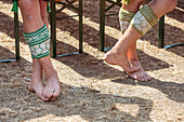 People in Bavarian costumes are barefoot on the dry ground beside beer banks
