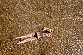 Young woman with black bikini is located in the shallow water of the river Isar in the flaucher, view from above