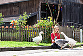 Blond girl sitting in front of a cottage garden and feed your tame geese