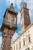 The Colonna Antica column on Piazza delle Erbe in front of the Lamberti Tower, Verona, Veneto, Italy