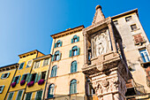 The Colonna Antica column on Piazza delle Erbe in front of houses in the old town, Verona, Veneto, Italy