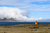 tiny orange lighthouse and sea fog at the eastfjords of Iceland