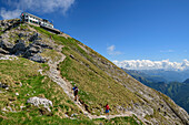 Several persons hiking, hut rifugio Brioschi at summit of Grignone in background, Grignone, Grigna, Bergamasque Alps, Lombardy, Italy