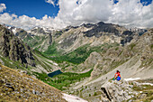 Woman hiking sitting on rock and looking towards valley, mountain lake and Cottian Alps in background, Val Maira, Cottian Alps, Piedmont, Italy