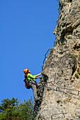 Woman climbing fixed rope route, Ferrata di Camoglieres, Val Maira, Cottian Alps, Piedmont, Italy
