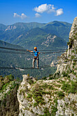 Woman climbing fixed rope route crossing ropeway, Ferrata di Camoglieres, Val Maira, Cottian Alps, Piedmont, Italy