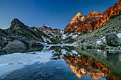 Monviso in alpenglow reflecting in mountain lake, Monte Viso, Monviso, valley valle di Po, Cottian Alps, Piedmont, Italy