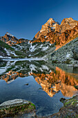 Monviso in alpenglow reflecting in mountain lake, Monte Viso, Monviso, valley valle di Po, Cottian Alps, Piedmont, Italy