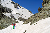 Man and woman hiking at Giro di Monviso ascending through snow towards Colle delle Traversette, Giro di Monviso, Monte Viso, Monviso, valley valle di Po, Cottian Alps, Piedmont, Italy