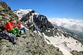 Mann und Frau beim Wandern machen am Colle delle Traversette Pause, Giro di Monviso, Monte Viso, Monviso, Valle di Po, Cottische Alpen, Piemont, Italien