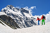 Man and woman hiking ascending through snow at Giro di Monviso towards Monviso, Giro di Monviso, Monte Viso, Monviso, Cottian Alps, France