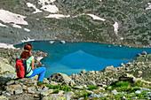 Frau beim Bergsteigen sitzt vor herzförmigem See Lago Chiaretto, Giro di Monviso, Monte Viso, Monviso, Cottische Alpen, Piemont, Italien