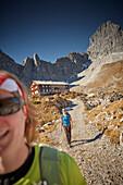 two women descending from Lamsenjoch alpine hut, Lamsenspitze in the back,  Eastern Karwendel Range, Tyrol, Austria