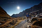 Two hikers leaving Lamsenjoch alpine hut,  Eastern Karwendel Range, Tyrol, Austria
