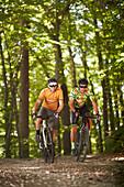 Zwei junge Männer fahren auf Gravel bikes über Feldweg, Münsing, Bayern, Deutschland