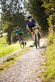 two young men on gravel bikel on a gravel road, Muensing, bavaria, germany